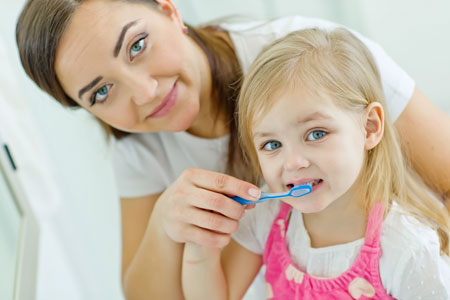 Mom and Daughter brushing their teeth - Pediatric Dentist in Rochester, MN